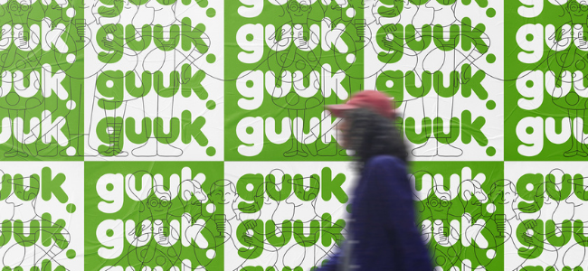 """Person walking in front of wall of green and white posters with the words """"guuk"""""""