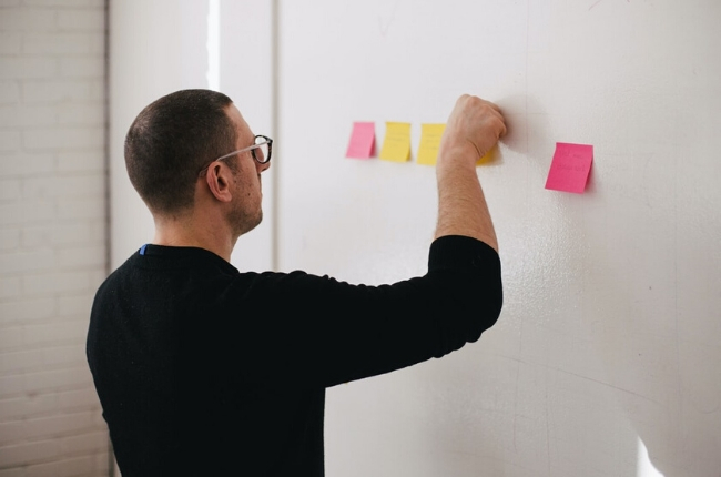 man choosing the right KPIs with stickie notes