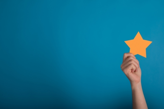 person holding a gold star against a blue backgound