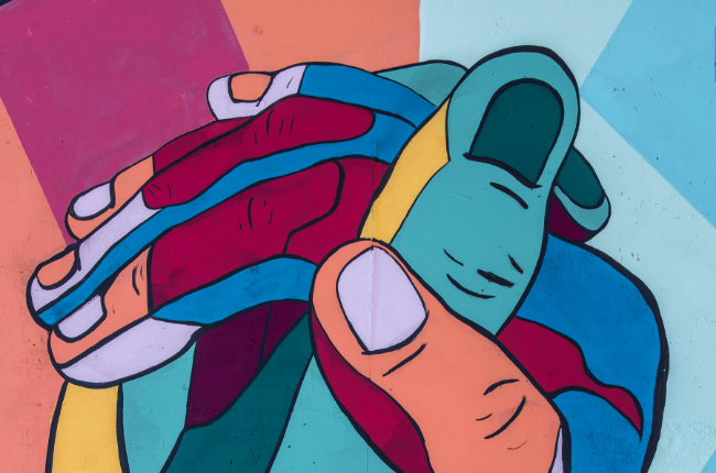 Color-block mural of two hands holding each other